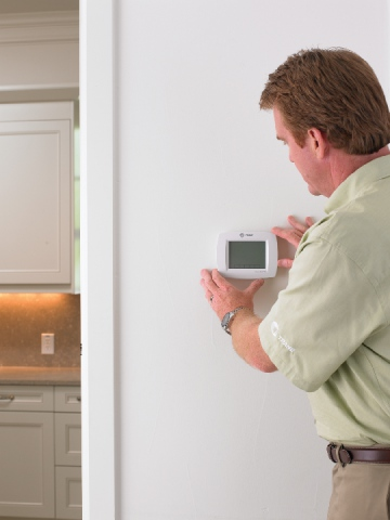 A technician looks at the thermostat in a Lewisville home