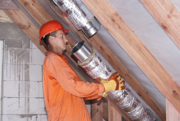A professional installs new air ducts in an attic