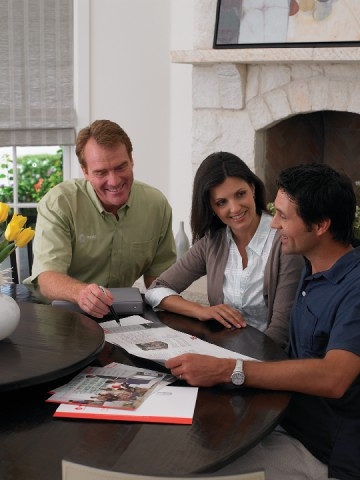 An Air Conditioning installer discusses options with a Coppell Homeowner
