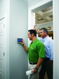 A Tech shows a Denton homeowner the basics of his new AC Control