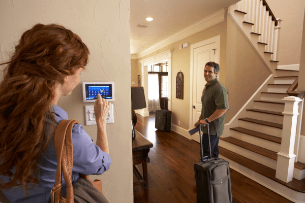 Woman controls thermostat while man with suitcase prepares to leave home