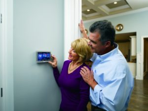 A woman adjusts the AC temperature while her husband looks on