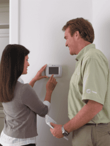 Woman adjusting thermostat while talking with man