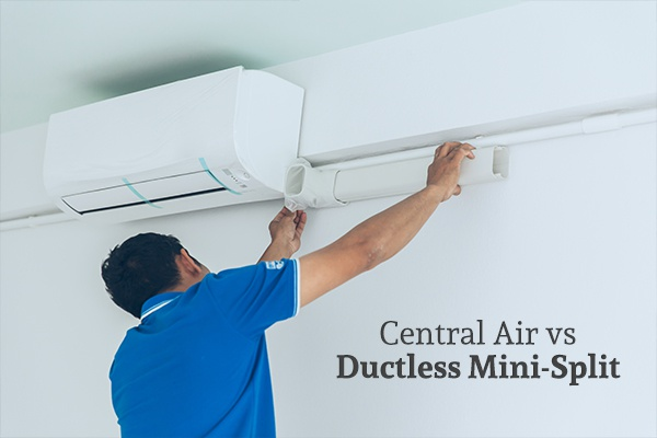An HVAC technician installing an air conditioner above the words central air vs ductless mini-split